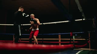 The boxer and his coach in the ring practice a series of punches and slopes. The camera moves behind the ropes. Overall plan