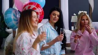 The bridesmaids sitting in a circle bumping glasses with champagne wishes and say happy for the impending marriage. Congratulations on the happy event. Women's pre-wedding party, the average plan
