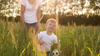 The concept of a happy family. In the rye field the kid walks across the field in the sun setting sun looking into the camera Mom stands behind