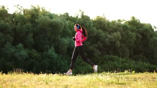 The girl runs at sunset in the Park along the pond and listening to music in headphones