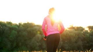 The girl warms up early in the morning before training preparing for a run in the sun