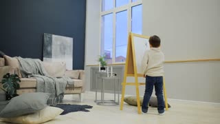 The little boy in the living room of the house draw on the Board with markers a child's drawing. Pre-school education