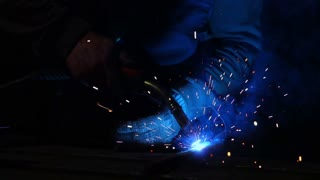 The welder works in a mask in slow motion. Sparks fly in different directions. Blue color glow welding. Work with steel materials