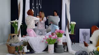 Three young sexy women pillow fighting at a slumber party in honor of the wedding. Beautiful woman laughing and smiling playfully. Pajama party.