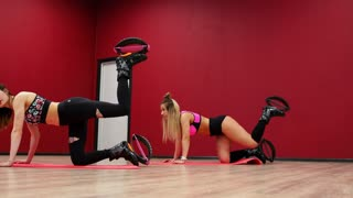 Two beautiful sports girls perform an active fat-burning workout jumping like a kango jump in special fitness shoes. Cardio workout for endurance. Exercise for the muscles of the buttocks