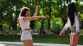 Two beautiful young girls in sexy clothes are laughing and dancing while riding on Segway in the Park on the weekend