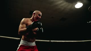 Two boxers sparring in the ring striking each other. Dynamic camera movement