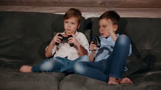 Two brothers sitting on the couch and very emotional playing video games with wireless joystick