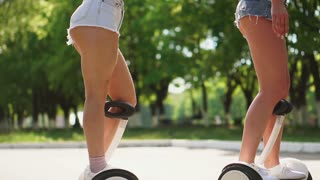 Two girlfriends in short denim shorts and white t-shirts are having fun on a Sunny day riding in slow motion on GyroScooter