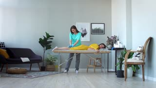 Two girls in a beauty salon master in a Bathrobe and gloves doing the procedure to remove hair on the legs with a sugar mixture