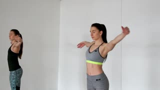 Two girls in sports legals on a white background in the gym conduct a Pilates class