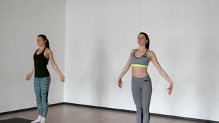 Two girls warm up after a workout share a deep breath with raising their hands. In the white gym