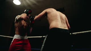 Two men without t-shirts in the ring hold a duel. Dynamic camera movement