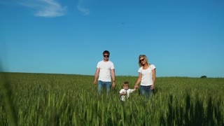 Walking family in the field with one child in white t-shirts