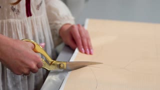 Young female designer with tape-line on her neck standing in dressmaking studio and drawing lines with chalk and rule. Female couturier in atelier cutting out a pattern for future clothes.