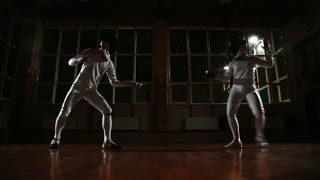Young man and woman dressed in costumes for fencing practice in the sports hall. Back on the background it is snowing. Horizontal movement of the camera right