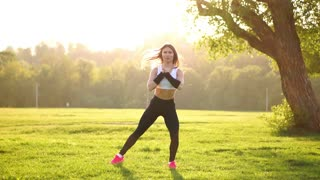 Young muscular fitness woman doing squats exercise in the nature.