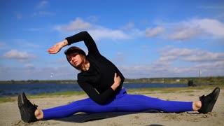 Young woman doing yoga exercise on summer sand beach at sunset, workout