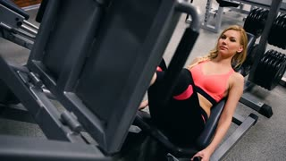 Young woman working her quads at machine press in the gym. Pretty Hispanic brunette exercising in a simulator in a gym