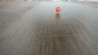 male hand spinning red cube on grey laminate slow motion