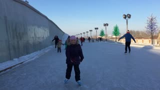A little girl skates on ice in winter. Girl sticking out tongue. Front view. Outdoors handheld shot.