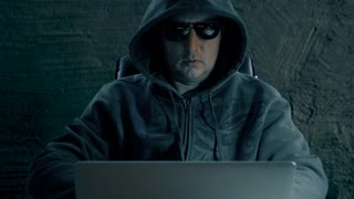 A man in hood and glasses sitting at table and coding on laptop. Dark night. Hacker in glasses working at computer. Coding man at concrete background. Front view close up.