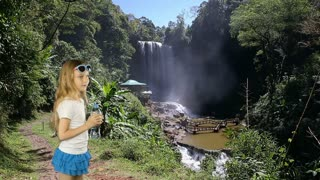 A young girl stands near a waterfall in the jungle and drinks crystal clear water from a bottle. A tropical forest and a huge waterfall. Healthy lifestyle. Adventures in the forest with fresh water.