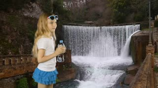 A young girl stands near the waterfall of the old city and drinks crystal clear water from the bottle. Stone fence and paving stones. Freshness of clean water. Have same clip with Alpha Channel.