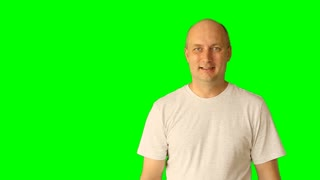 Adult white caucasian man laughing and make gestures with green screen. Draw line touch tap virtual screen. Upper half close-up shot. Male white t-shirt. Clip with Premultiplied matted Alpha Channel.