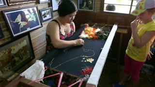 Asian woman is embroidering a silk picture.