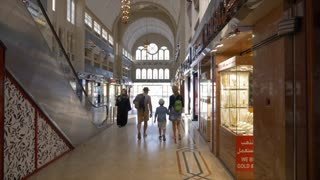 Dubai, UAE - January 18, 2018: tourist family walking in famous gold souk in Dubai city UAE. People walking inside gold store with traditional arabian architecture and expensive jewelry showcases.