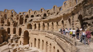 El Jem, Tunisia - 10 June 2018: group of tourists visiting antique amphitheater Gordian while historic excursion. Tourist walking in old amphitheatre.