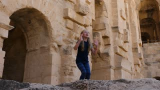 Joyful girl teenager dancing on background stony walls in ancient fortress