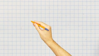 Male hand with pen writing on white checkered background close up
