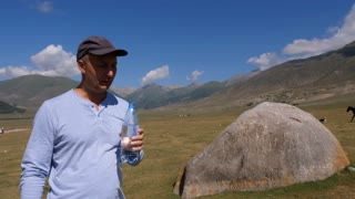 Man drinks water from bottle at hiking mountain, hills and highlands background