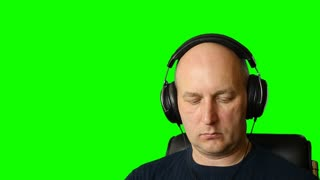 Man is listening music with headphones at green screen background.