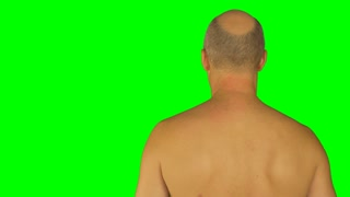 Man rubbing his shoulders with left hand. Back view naked waist up.