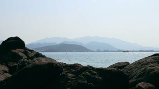 Panorama of seascape with stones blue ocean and skyline sity.