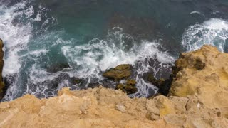 Sea waves splashing about stony cliff top view. Water waves breaks to rocky cape