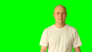 The adult man smiles and nods his shaking head. He gestures with his hands and head. Studio shooting model on a green background. Prepared as a template for advertising.