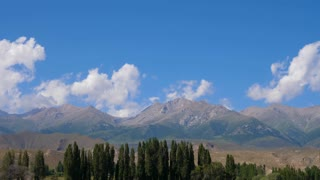 Tian Shan mountains with trees and clouds on blue sky, timelapse view