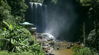 Waterfall in jungle and tourists