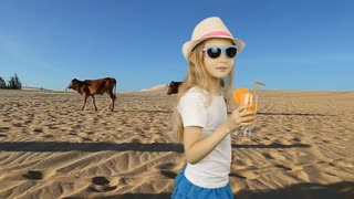 Young caucasian girl drink orange juice. Young girl in sahara desert feeling thirst. Very hot warm climat in desert. Fresh juice of orange fruit drinking walking in hat summer day.