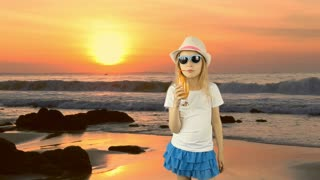Young caucasian girl standing and drinking orange juice cocktail through straw. Sunset sea coast horizon. Girl drinking orange juice. Have same clip with transparent background Alpha Channel.