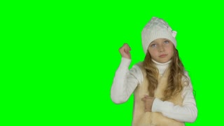 Young girl in white knitted hat show gestures. Victory sign and thumbs up gestures. Young girl hands gestures. New year christmas winter concept. Keyed. Solid green background instead alpha channel.