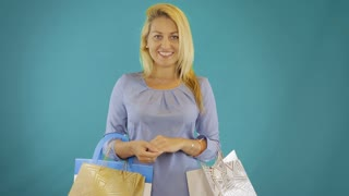 Young woman walk with shopping bag isolated at blue solid background. Front view.