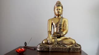 Big Buddha statue and Incense stick burning in incense burner and candle with lotus flower shape