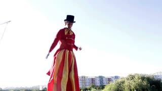 Busker street performer on Stilts jumping