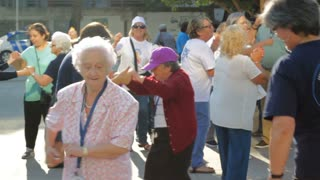 Group of seniors dance happily on the street