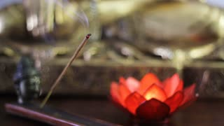 Incense stick burning in incense burner and candle with lotus flower shape